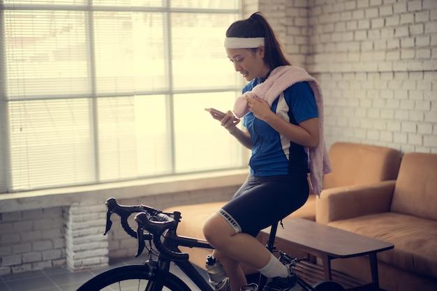 サイクリストがアプリケーションの統計情報をアップロードする彼女は自宅で自転車に乗っています