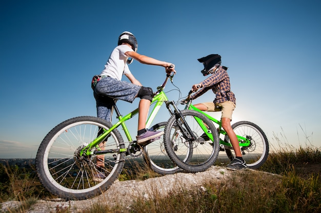 Cyclists with mountain bikes on the hill under blue sky
