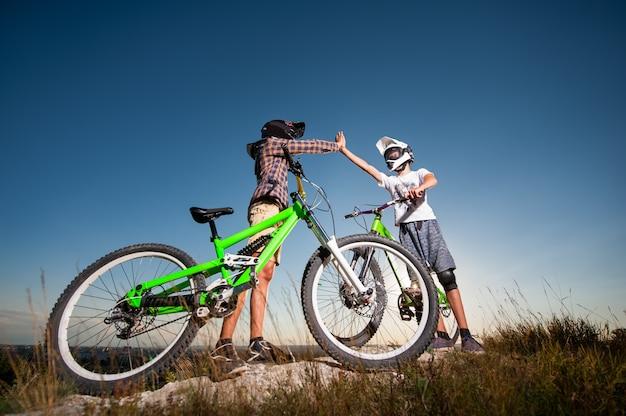 Велосипедисты с горными велосипедами на холме под голубым небом