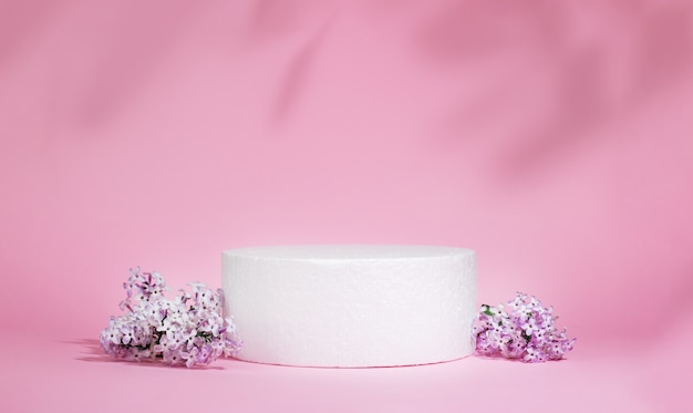 Cylindrical white podium on a pink background with hard shadows and lilac flowers. minimal empty cosmetic product presentation scene. geometric podium.