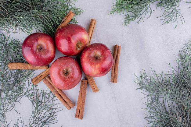 Ветви кипариса, палочки корицы и яблоки связываются вместе на белом фоне.