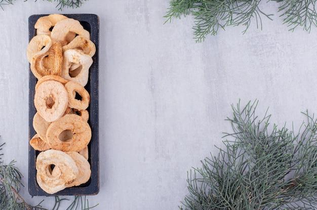 Rami di cipresso accanto a fette di mela essiccate in bundle su un piccolo vassoio su sfondo bianco.