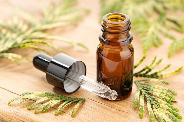 Бутылка эфирного масла кипариса на деревянном столе натюрморт