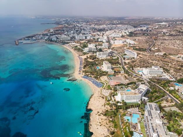 キプロスの美しい海岸線、ターコイズ色の地中海。地中海沿岸の住宅。ロングビーチのあるツーリストタウン。海での夏休み。上面図、航空写真。キプロス、アギアナパ。