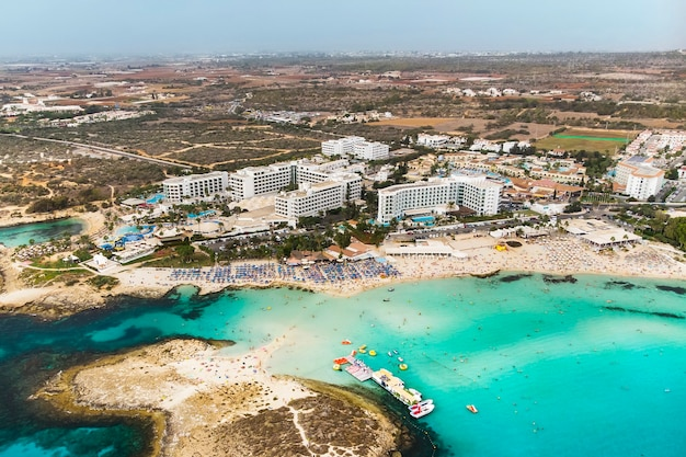 Cyprus beautiful coastline, mediterranean sea of turquoise color. houses on the mediterranean coast. tourist town. nissi beach. summer vacation at sea. top view, aerial view. cyprus, ayia napa.
