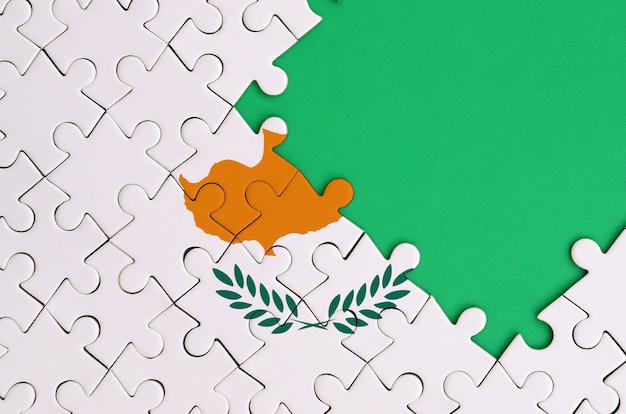 Cyprus flag is depicted on a completed jigsaw puzzle with free green copy space on the right side