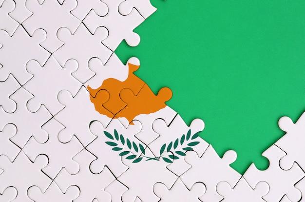 키프로스 깃발은 오른쪽에 무료 녹색 복사 공간이있는 완성 된 직소 퍼즐에 그려져 있습니다.