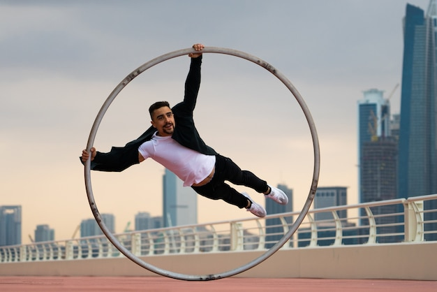 Cyr wheel artist wearing black and white smart clothes with cityscape of dubai during sunset.