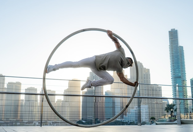 Cyr wheel artist with cityscape of dubai during sunset.