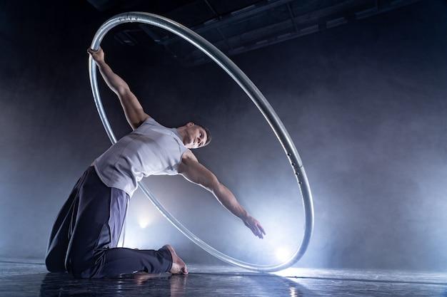 ステージで演奏するスモーク、暗い背景のcyrwheelサーカスアーティスト