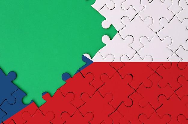 체코 국기는 왼쪽에 무료 녹색 복사 공간이있는 완성 된 직소 퍼즐에 그려져 있습니다.