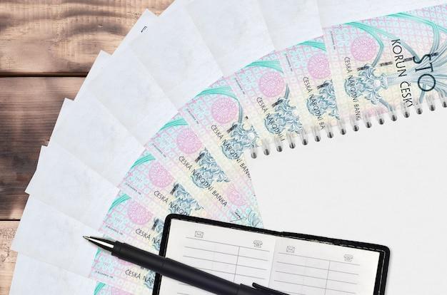 Вентилятор банкнот чешских крон и блокнот с записной книжкой и черной ручкой