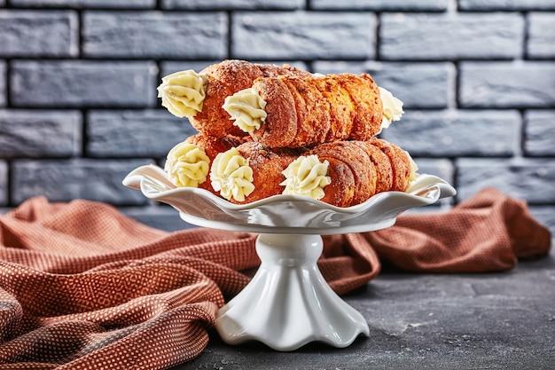 체코 크렘 롤 : 검은 벽돌 벽 앞에있는 흰색 케이크 스탠드에 제공되는 버터 크림 설탕으로 채워진 전통 과자