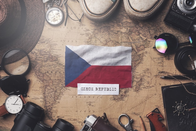 Czech republic flag between traveler's accessories on old vintage map. overhead shot