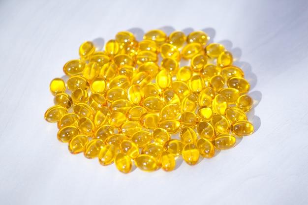 Желтые капсулы с витамином d, рыбий жир омега-3 с солнечным светом. здоровая и медицинская концепция.