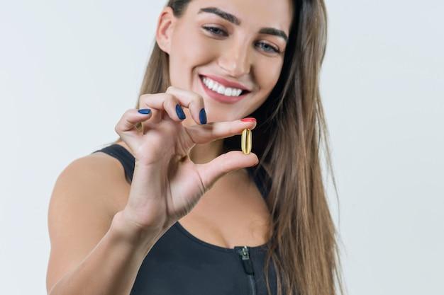 Молодая здоровая женщина в спортивной одежде с витамином d, e, a, рыбий жир, капсулы омега-3