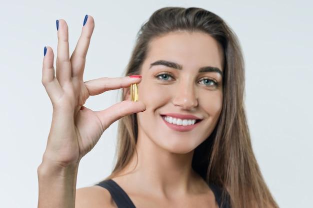 ビタミンd、e、aとスポーツウェアの若い女性
