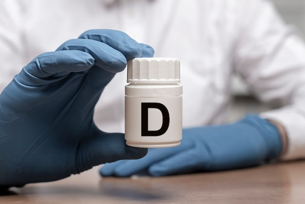 남성 의사 손에 항아리 또는 병에 d 비타민.