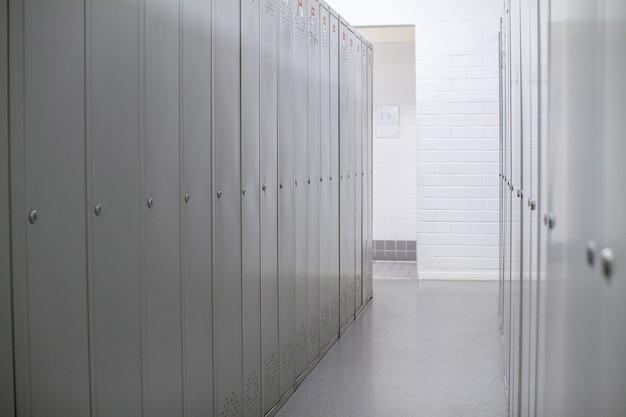 Ряд стальных серых шкафчиков вдоль белой стены. d