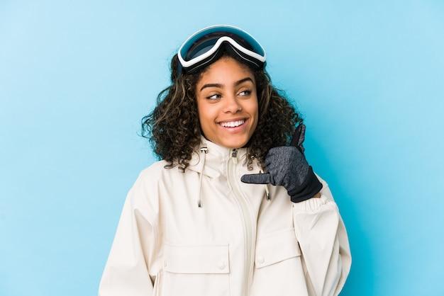 Молодая афро-американская женщина лыжника d показывая жест звонка мобильного телефона с пальцами.