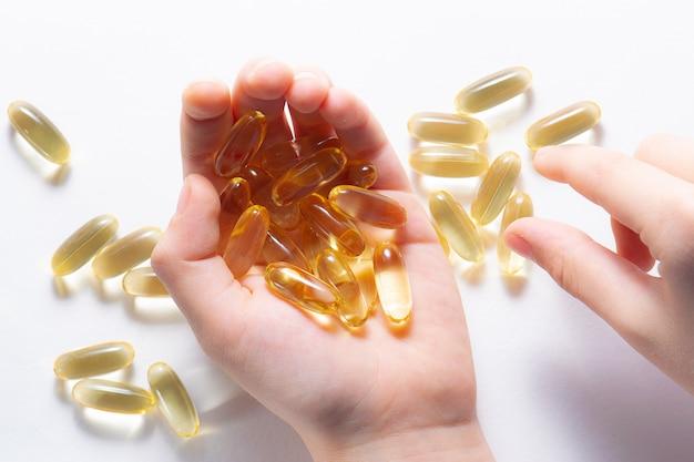 Капсулы масла печени трески с витамином d в руке ребенка на белой предпосылке.