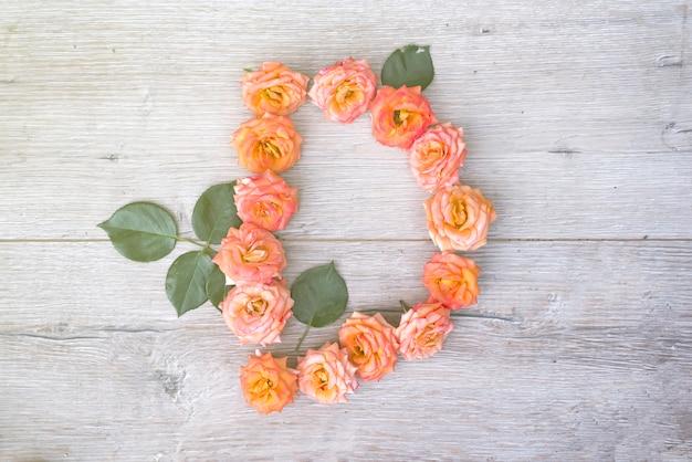 D、バラの花のアルファベットは、灰色の木製の背景に、平らな寝かせ