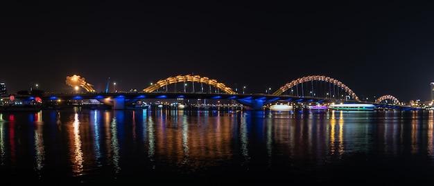 Ландшафт взгляда ночи моста дракона через реку на da nang, вьетнам.
