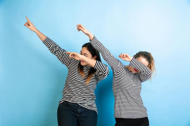 Dabbing. giovani donne emotive isolate sul muro blu sfumato. concetto di emozioni umane, esperienza facciale, amicizia, annuncio. bellissimi modelli femminili caucasici in abiti casual.