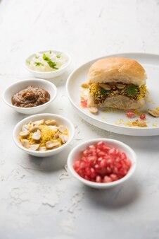 Дабели - это индийская закуска, которую подают с зернами граната и кинзой на белой керамической тарелке. это популярная еда на фестивале наваратри. Premium Фотографии