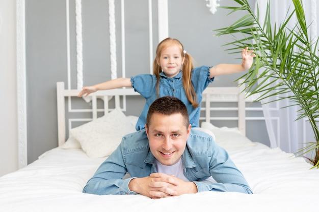 아빠와 아기 딸은 침대에서 집에서 놀고 껴안고 재미 있습니다.