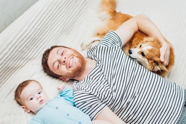 Папа и ребенок лежат на кровати с собакой