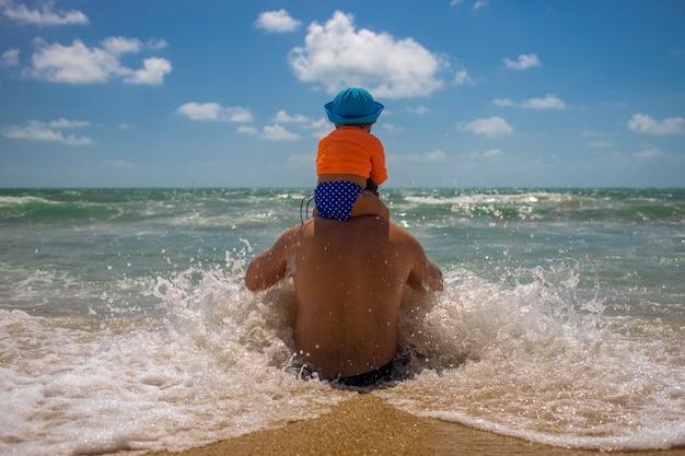 お父さんと赤ちゃんは波の中で遊ぶ。