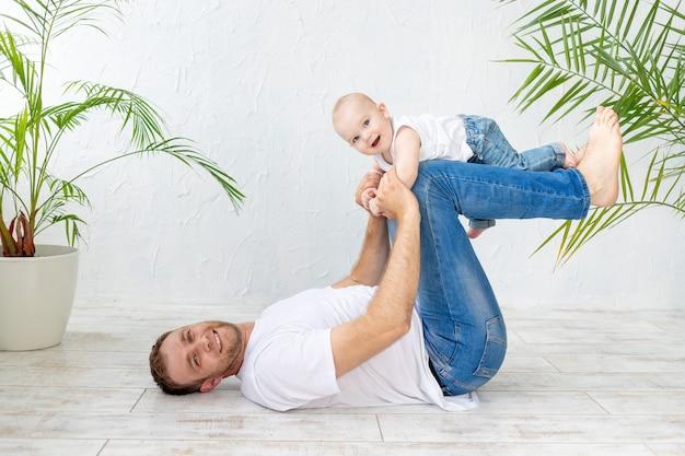 아빠와 아기 아들이 스포츠를하거나 흰색 배경, 행복한 아버지와 가족에서 즐거운 시간을 보내십시오.