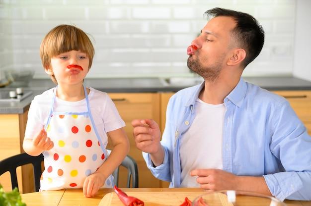 Папа и ребенок едят здоровые овощи