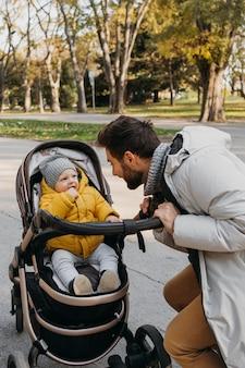 屋外のベビーカーでお父さんと子供