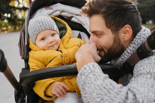自然の中で外のベビーカーでお父さんと子供