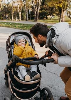 外のベビーカーでお父さんと子供