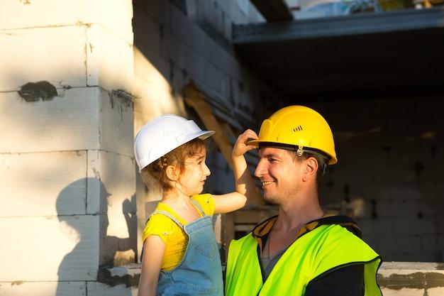 아빠와 딸은 미래의 집 건설 현장에 있습니다. 건축업자의 미래 직업의 선택은 아이에게 상속됩니다. 이사의 기대, 집의 꿈. 모기지, 대출