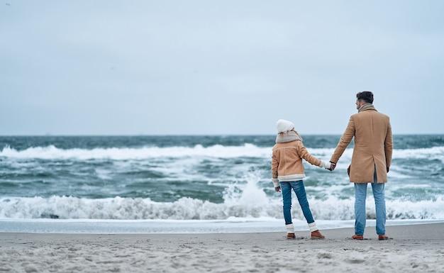 아빠와 딸은 겨울에 해변에서 파도 소리를 즐기며 바다를 바라보고 손을 잡고 있습니다.
