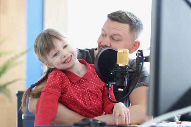 音楽に従事しているお父さんと娘は音楽のための耳の開発の近くにマイクがあります