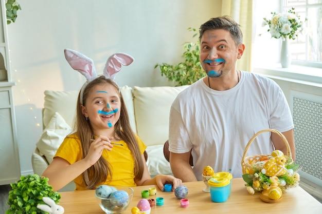 お父さんと娘の顔は卵を塗るために青い絵の具で染められています。テーブルの上にはイースターエッグと絵の具が入ったバスケットがあります。