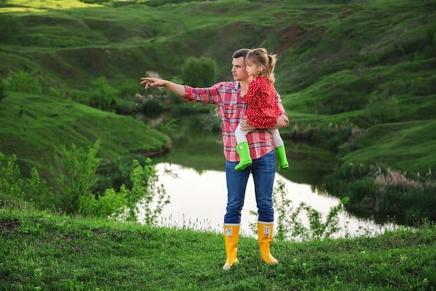 자연 속에서 밝은 고무 장화에 아빠와 딸