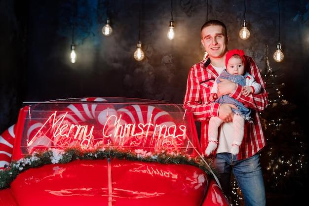 스튜디오에서 아빠와 딸 새해. 복고풍 빨간 차 근처의 가족은 겨울에 행복합니다.
