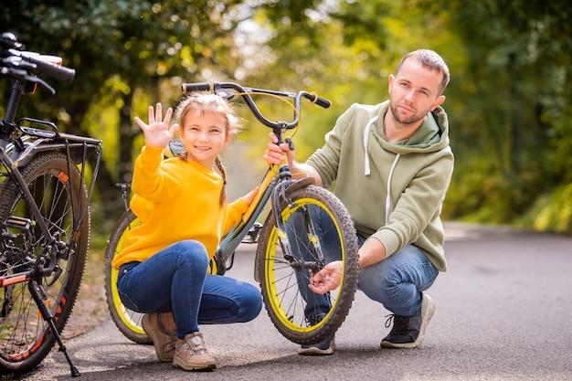 아빠와 딸은 공원의 가을 길에서 어린이 십대 자전거의 바퀴를 검사합니다.