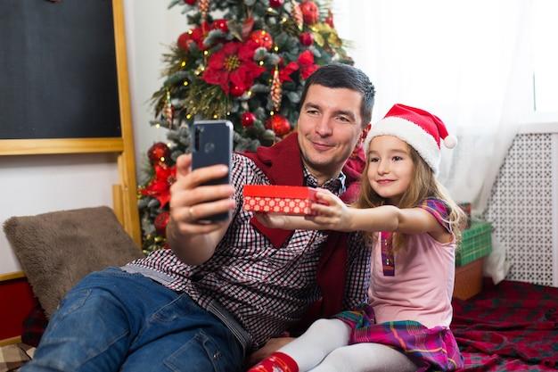 스마트 폰으로 크리스마스 트리 근처의 아빠와 딸이 셀카를 찍고 비디오 연결을 통해 의사 소통합니다. 크리스마스 인사, 선물 상자, 안녕하세요를 흔들며 산타 모자 소녀.