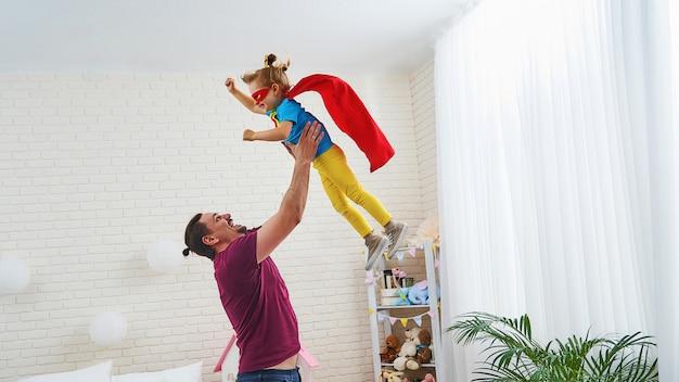Папа и дочь играют супергероев в детской комнате.