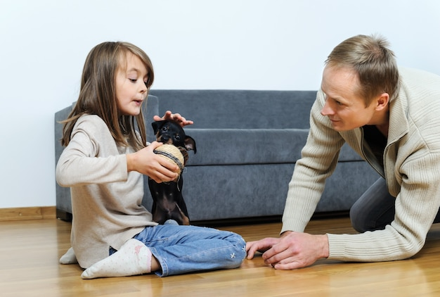 아빠와 딸이 방 바닥에 강아지와 함께 연주. 여자 아이가 개에게 공을주고 있어요.