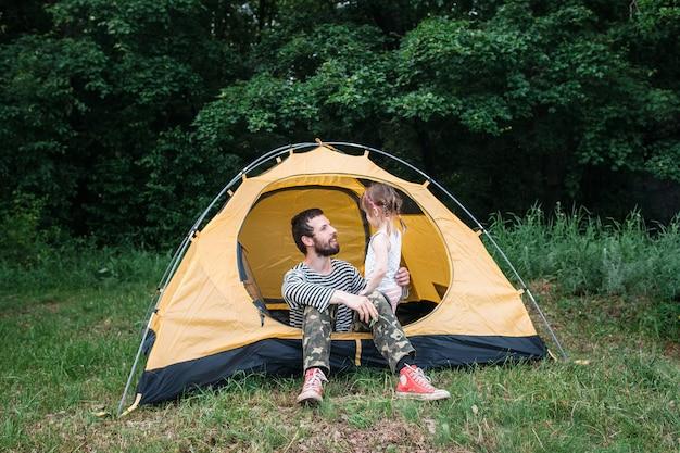 森のテントで休んでいるお父さんと娘