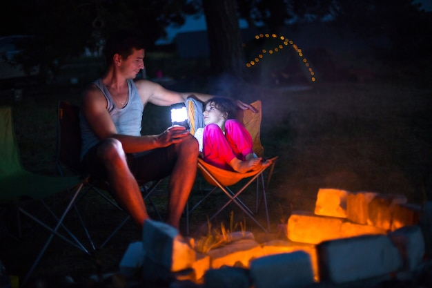 Папа с дочкой сидят ночью у костра на свежем воздухе, летом на природе. семейный поход, посиделки у костра. день отца, шашлык. фонарь и палатка для кемпинга
