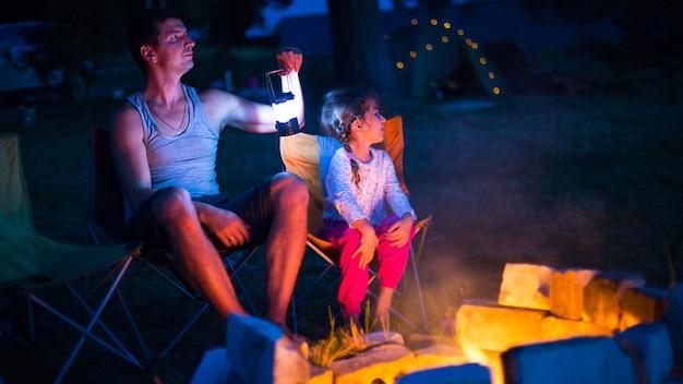 Папа с дочкой сидят ночью у костра на свежем воздухе, летом на природе.